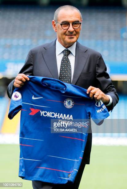 Chelsea's newly appointed manager, Maurizio Sarri, holds up a team football shirt as he poses for photographs on the pitch following his unveiling...