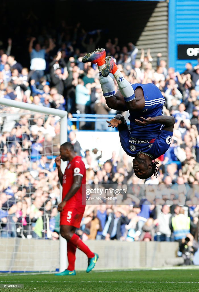 Chelsea's Nigerian midfielder Victor Moses (R) celebrates after scoring their third goal as Leicester City's English-born Jamaican defender Wes Morgan (L) reacts during the English Premier League football match between Chelsea and Leicester City at Stamford Bridge in London on October 15, 2016. / AFP / Adrian DENNIS / RESTRICTED TO EDITORIAL USE. No use with unauthorized audio, video, data, fixture lists, club/league logos or 'live' services. Online in-match use limited to 75 images, no video emulation. No use in betting, games or single club/league/player publications. /