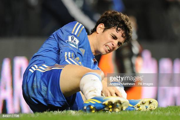 Chelsea's Oscar lies clutches his ankle in pain