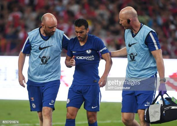Chelsea's Pedro leaves the field after a collision with Arsenal's David Ospina during their preseason football match in Beijing's National Stadium...