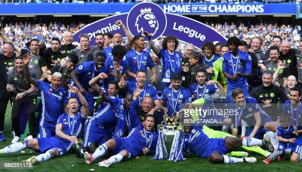 TOPSHOT Chelsea's players gather on the pitch with the English Premier League trophy as they celebrate their league title win at the end of the...