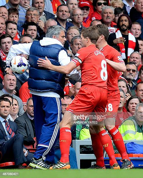 Chelsea's Portuguese manager Jose Mourinho keeps the ball away from Liverpool's English midfielder Steven Gerrard during the English Premier League...