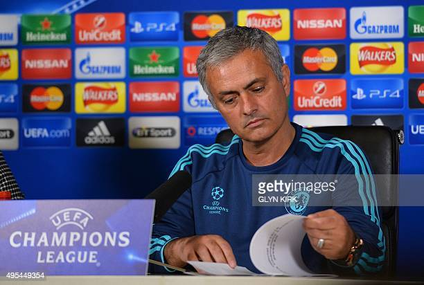 Chelsea's Portuguese manager Jose Mourinho reads the press stats at a press conference at Chelsea's training ground in Cobham in south west London on...