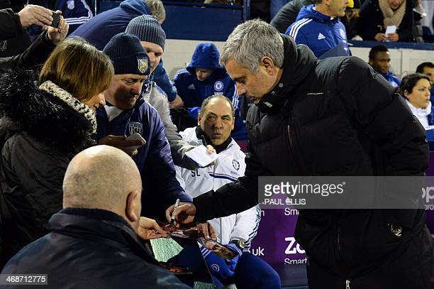 Chelsea's Portuguese manager Jose Mourinho signs autographs as he arrives for the English Premier League football match between West Bromwich Albion...