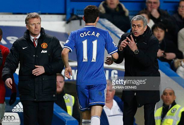 Chelsea's Portuguese manager Jose Mourinho talks with Chelsea's Brazilian midfielder Oscar as Manchester United's Scottish manager David Moyes makes...