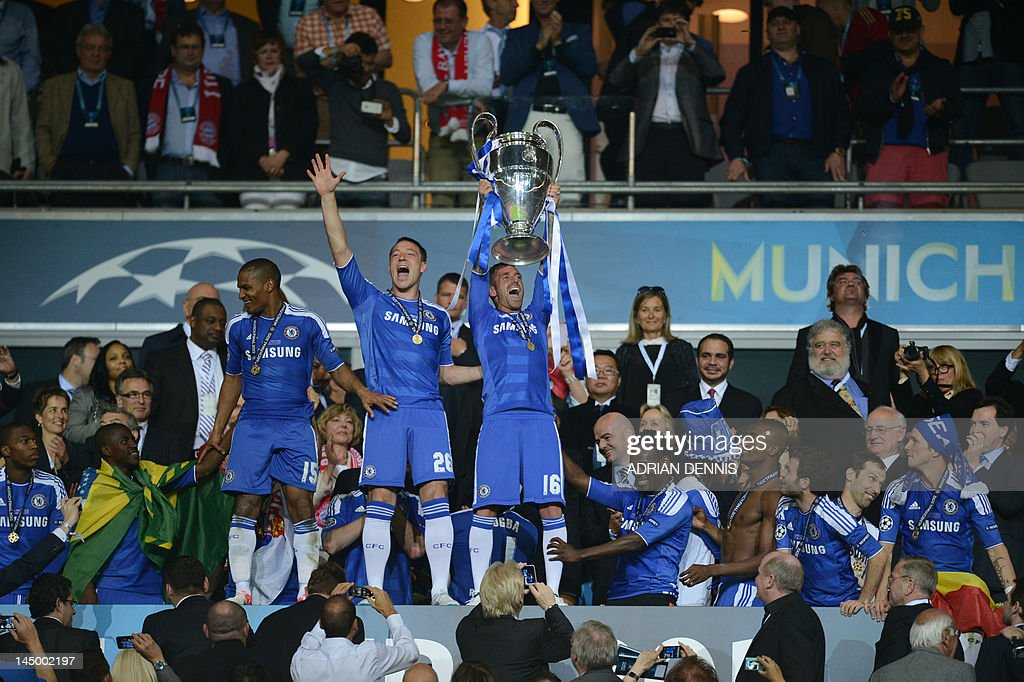 Chelsea's Portuguese midfielder Raul Meireles (C) holds the trophy next to John Terry (L) after the UEFA Champions League final football match between FC Bayern Muenchen and Chelsea FC on May 19, 2012 at the Fussball Arena stadium in Munich. Chelsea won 4-3 in the penalty phase.