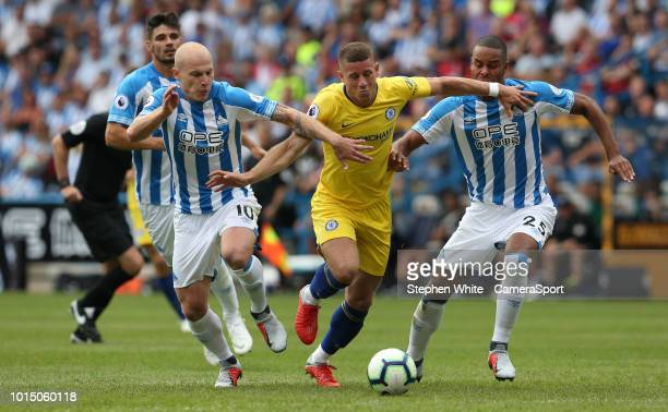 Chelsea's Ross Barkley battles with Huddersfield Town's Aaron Mooy and Mathias Zanka Jorgensen during the Premier League match between Huddersfield...