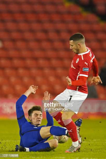 Chelsea's Scottish midfielder Billy Gilmour slides in to tackle Barnsley's English striker Conor Chaplin during the English FA Cup fifth round...