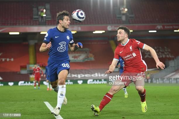 Chelsea's Spanish defender Cesar Azpilicueta heads the ball as he defends against Liverpool's Portuguese striker Diogo Jota during the English...