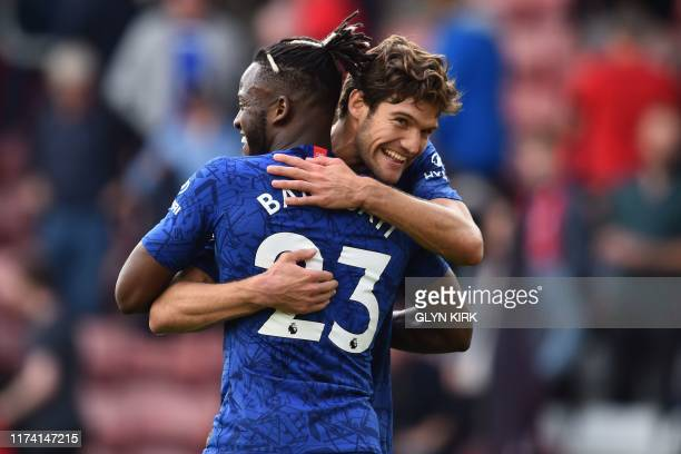 Chelsea's Spanish defender Marcos Alonso embraces Chelsea's Belgian striker Michy Batshuayi as they celebrate on the pitch after the English Premier...