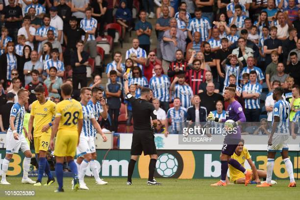Chelsea's Spanish defender Marcos Alonso is down as referee Chris Kavanagh waves a yellow card prior to awarding a penalty during the English Premier...
