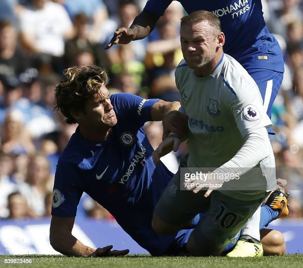 Chelsea's Spanish defender Marcos Alonso tackles Everton's English striker Wayne Rooney during the English Premier League football match between...