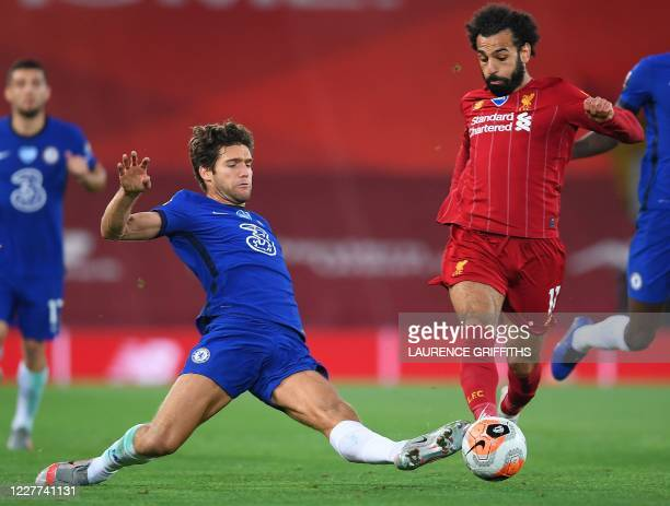 Chelsea's Spanish defender Marcos Alonso tackles Liverpool's Egyptian midfielder Mohamed Salah during the English Premier League football match...
