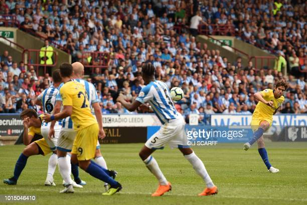 Chelsea's Spanish defender Marcos Alonso takes a free kick into the wall during the English Premier League football match between Huddersfield Town...