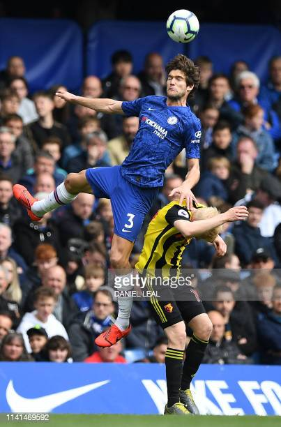 Chelsea's Spanish defender Marcos Alonso vies to header the ball against Watford's English midfielder Will Hughes during the English Premier League...