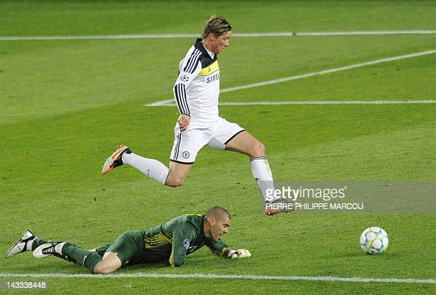 Chelsea's Spanish forward Fernando Torres jumps over Barcelona's goalkeeper Victor Valdes to score and win the match during the UEFA Champions League...
