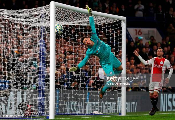 Chelsea's Spanish goalkeeper Kepa Arrizabalaga dives but the ball hits the post and subsequently hits him for Ajax's third goal during the UEFA...
