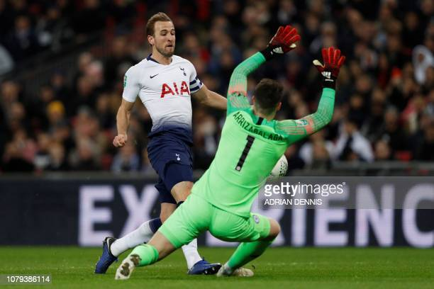 Chelsea's Spanish goalkeeper Kepa Arrizabalaga fouls Tottenham Hotspur's English striker Harry Kane to concede a penalty during the English League...
