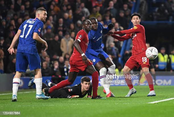Chelsea's Spanish goalkeeper Kepa Arrizabalaga watches the ball after making a save from Liverpool's Japanese midfielder Takumi Minamino during the...