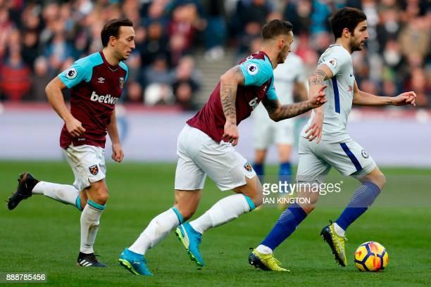 Chelsea's Spanish midfielder Cesc Fabregas is chased by West Ham United's English midfielder Mark Noble and West Ham United's Austrian midfielder...