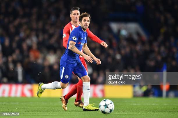 Chelsea's Spanish midfielder Cesc Fabregas is marked by Atletico Madrid's Spanish striker Fernando Torres during a UEFA Champions League Group C...