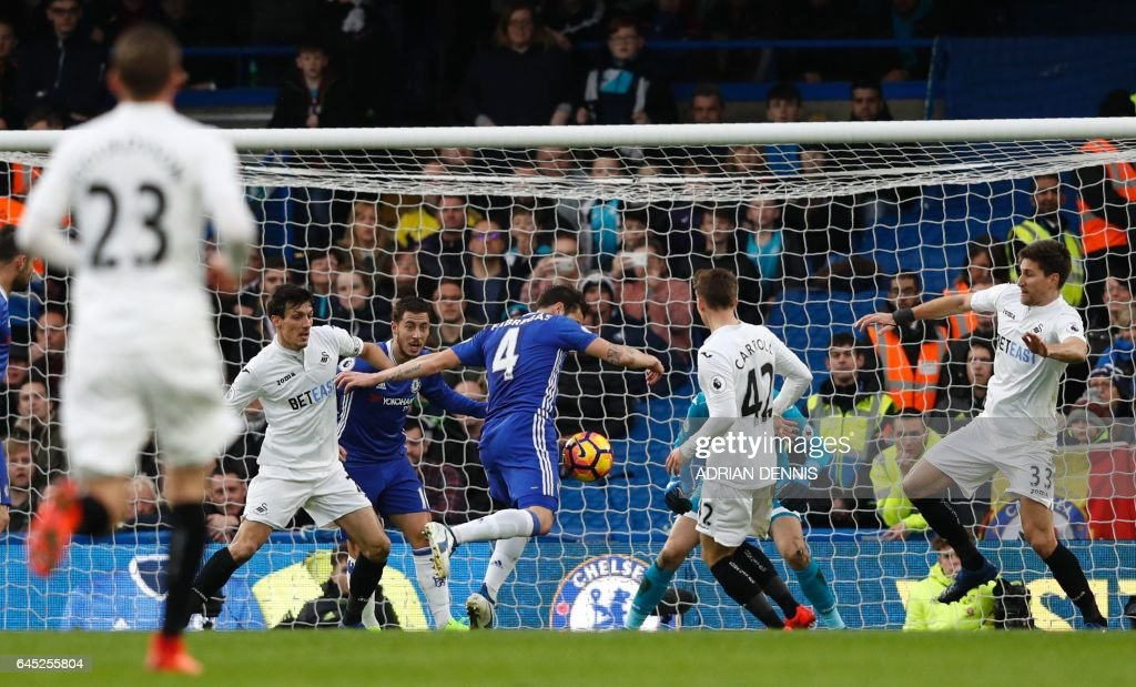 Chelsea's Spanish midfielder Cesc Fabregas (C) scores the opening goal during the English Premier League football match between Chelsea and Swansea at Stamford Bridge in London on February 25, 2017. / AFP / Adrian DENNIS / RESTRICTED TO EDITORIAL USE. No use with unauthorized audio, video, data, fixture lists, club/league logos or 'live' services. Online in-match use limited to 75 images, no video emulation. No use in betting, games or single club/league/player publications. /