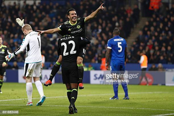 Chelsea's Spanish midfielder Pedro celebrates in the arms of Chelsea's Brazilian midfielder Willian after scoring their third goal during the English...