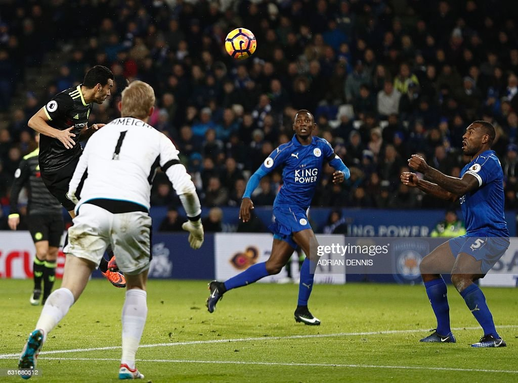 Chelsea's Spanish midfielder Pedro (L) heads home their third goal past the watching Leicester City's Danish goalkeeper Kasper Schmeichel (L), Leicester City's Nigerian midfielder Wilfred Ndidi and Leicester City's English-born Jamaican defender Wes Morgan (R) during the English Premier League football match between Leicester City and Chelsea at King Power Stadium in Leicester, central England on January 14, 2017. / AFP / Adrian DENNIS / RESTRICTED TO EDITORIAL USE. No use with unauthorized audio, video, data, fixture lists, club/league logos or 'live' services. Online in-match use limited to 75 images, no video emulation. No use in betting, games or single club/league/player publications. /