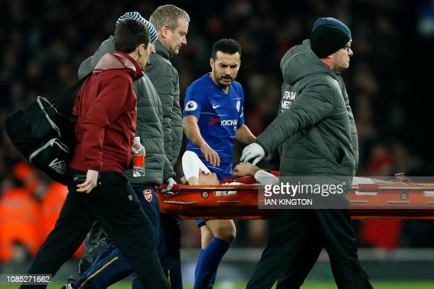Chelsea's Spanish midfielder Pedro shows concern for Arsenal's Spanish defender Hector Bellerin as he is taken off on a stretcher after picking up an...