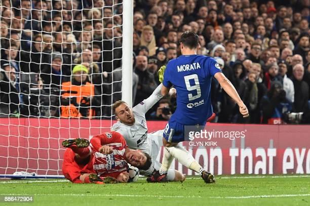 Chelsea's Spanish striker Alvaro Morata has a shot blocked by Atletico Madrid's Uruguayan defender Jose Gimenez and Atletico Madrid's Slovenian...