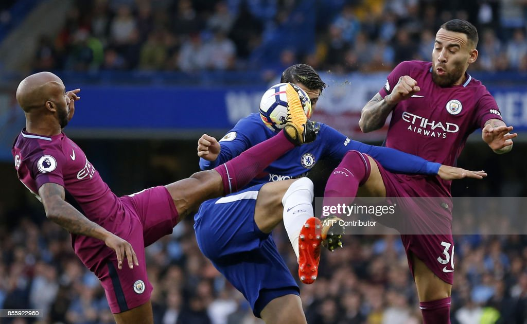 TOPSHOT - Chelsea's Spanish striker Alvaro Morata (C) vies with Manchester City's English midfielder Fabian Delph (L) and Manchester City's Argentinian defender Nicolas Otamendi (R) during the English Premier League football match between Chelsea and Manchester City at Stamford Bridge in London on September 30, 2017. / AFP PHOTO / Ian KINGTON / RESTRICTED TO EDITORIAL USE. No use with unauthorized audio, video, data, fixture lists, club/league logos or 'live' services. Online in-match use limited to 75 images, no video emulation. No use in betting, games or single club/league/player publications. /