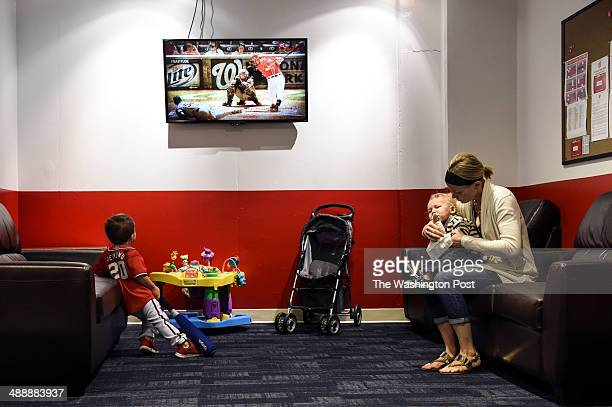 Chelsey Desmond right holds her son Cruz while Grayson watches the Washington Nationals platy the San Diego Padres from the family room of Nationals...