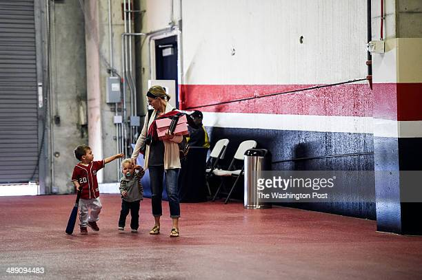 Chelsey Desmond right walks into Nationals Park with her two sons Grasyon left and Cruz center to watch to watch their dad Washington Nationals short...