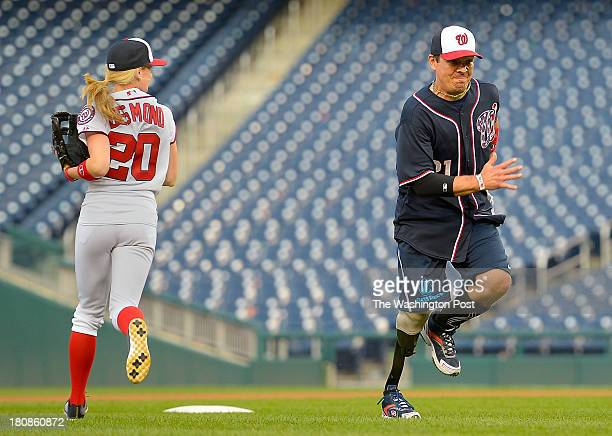 Chelsey Desmond wife of Nationals short stop Ian Desmond runs to cover 2nd base as US Air Force's Mike Dreyer with a artificial leg below the right...