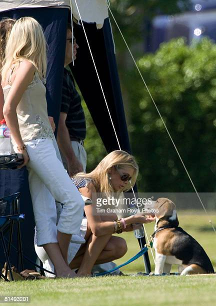 Chelsy Davy among friends strokes a beagle puppy dog while watching Prince Harry at Cirencester Park Polo Club in a charity polo match raising money...