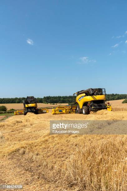 Cheltenham Gloucestershire England Two combine harvesters working to harvest a field of barley which when dried be sent to a brewery to produce beer