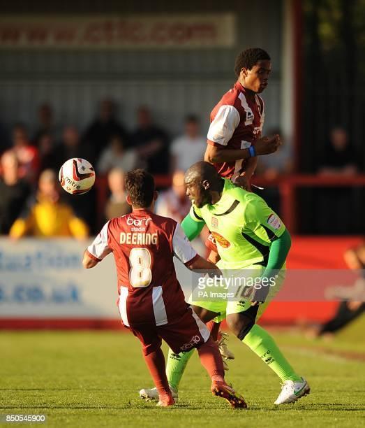 Cheltenham Town's Sam Deering and Sido Jombati battle for the ball with Cheltenham Town's Adebayo Akinfenwa