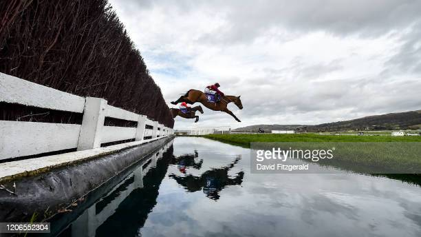 Cheltenham United Kingdom 11 March 2020 Minella Indo with Rachael Blackmore up clear the water jump first time round ahead of Allaho with Paul...