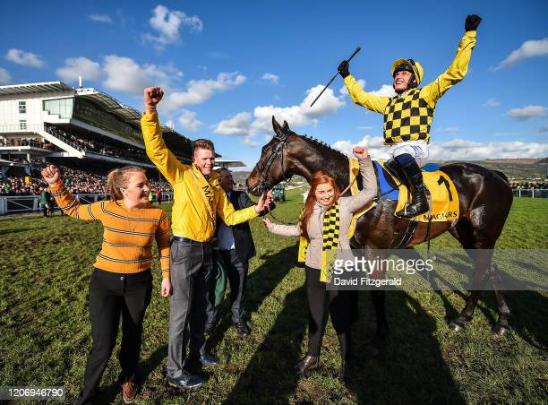 Cheltenham United Kingdom 13 March 2020 Paul Townend on Al Boum Photo celebrates with Stable Hand Paul Roche second from left and winning connections...
