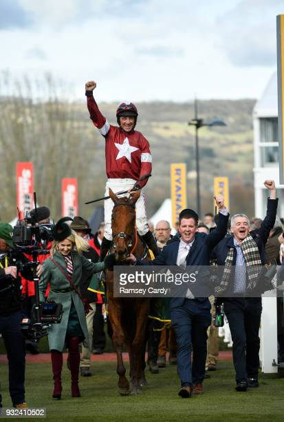 Cheltenham United Kingdom 15 March 2018 Jockey Davy Russell celebrates as enters the winners' enclosure with the groom owner Michael O'Leary right...
