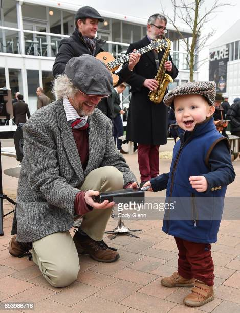 Cheltenham United Kingdom 16 March 2017 Harry Almond age 2 from Thirsk England playes the cow bell with the Hipcats comprised of from left David...