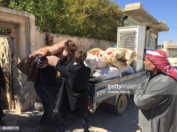 Chemical gas attack survivor residents load their goods on a pickup truck before leaving the town after yesterday's suspected chlorine gas attack in...
