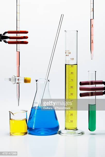 Chemical lab glassware: burette over beaker, Erlenmeyer flask with stirring rod, graduated cylinder, pipette over test tube