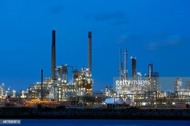 chemical plant illuminated at dusk in netherlands - gas refinery stock photos and pictures