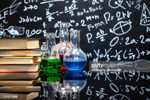 chemical sciences education concept,classroom desk and drawn blackboard of chemistry teaching with books and instruments. chemical sciences education concept. - chemical formula stock pictures, royalty-free photos & images