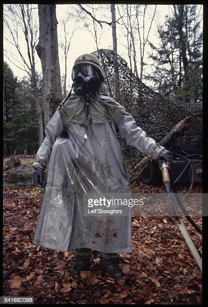A chemical specialist in training at Fort Drum wears full protective gear as she learns methods of decontaminating sites and people from chemical...