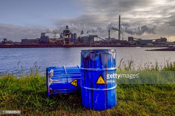 chemical waste drums in front of heavy industry - inquinamento ambientale foto e immagini stock