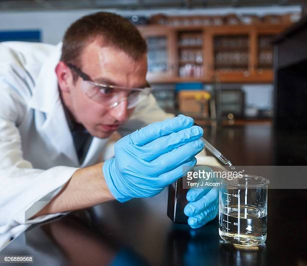 chemist adding sulfuric acid to a beaker with a dropper - sulfuric acid stock photos and pictures