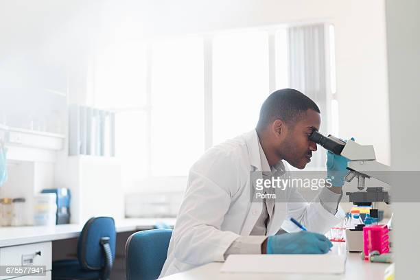 Chemist analyzing through microscope at laboratory