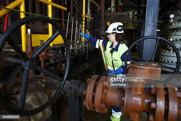 A chemist collects an oil sample for quality testing on the Casablanca oil platform operated by Repsol SA in the Mediterranean Sea off the coast of...